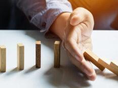 Eine Hand stoppt den Dominoeffekt. Das Umfallen der Dominosteine wird gestoppt.