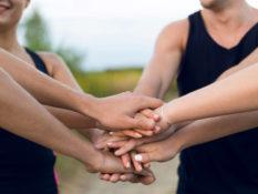 Eine Gruppe Menschen hält die Hände zusammen, verbinden sich, arbeiten Hand in Hand.